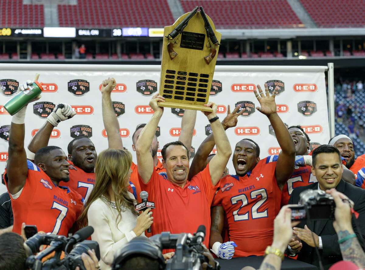 Sam Houston State Bearkats Head Coach, K.C. Keeler holds up the trophy after beating the Stephen F. Austin Lumberjacks 34-28 during the 90th Battle Of The Piney Woods on Saturday, October 3, 2015 at NRG Stadium.