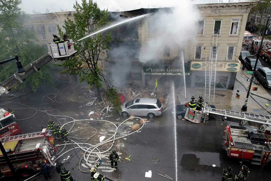 Firefighters work at the at the scene of an explosion at a three-story building in the Borough Park neighborhood in the Brooklyn borough of New York, Saturday, Oct. 3, 2015. Firefighters in New York say one person is dead and three more have been injured in an apparent explosion and fire. (AP Photo/Mary Altaffer) Photo: Mary Altaffer, STF / AP