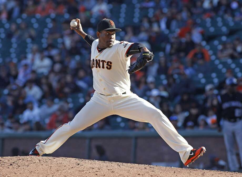 Santiago Casilla throws to the plate during Sunday's victory against the Rockies. Photo: George Nikitin, Associated Press