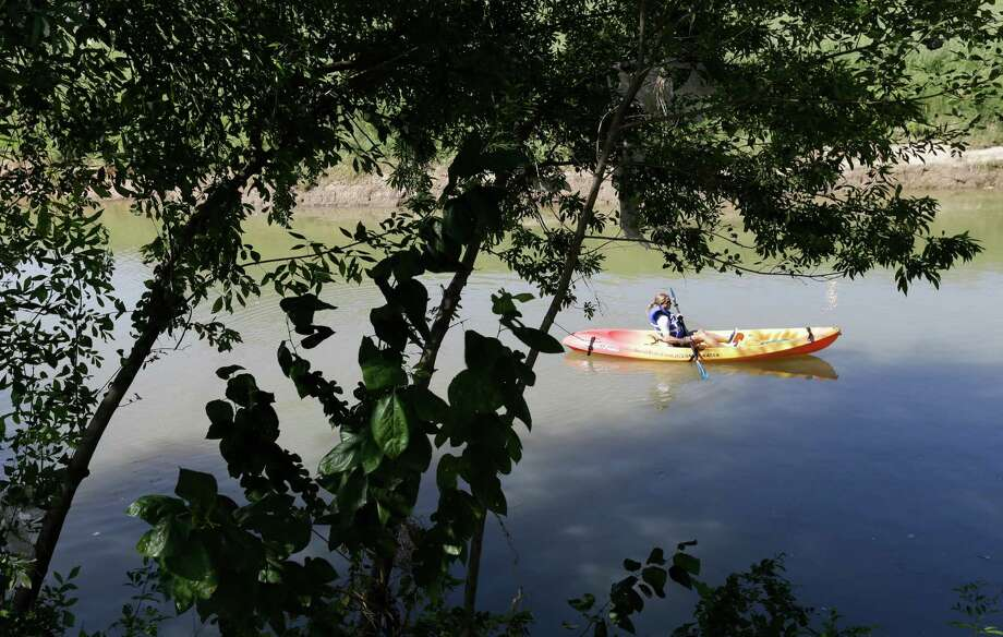 A kayaker moves gracefully along the water during the Buffalo Bayou Park grand opening Saturday, which attracted thousands. Photo: Melissa Phillip, Staff / © 2015 Houston Chronicle