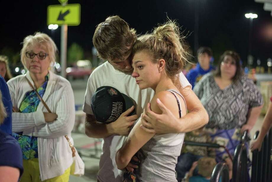 Jordan Cooper holds Ashley McIntyre (R)  during a vigil for victims of a mass shooting in Roseburg, Oregon, on October 2, 2015. The 26-year-old gunman behind America's latest mass shooting hoarded an arsenal of weapons, authorities said, describing him as a loner with a gripe against religion. AFP PHOTO / CENGIZ YAR JRCengiz Yar Jr./AFP/Getty Images Photo: CENGIZ YAR JR., Stringer / AFP / Getty Images / AFP PHOTO / CENGIZ YAR JR