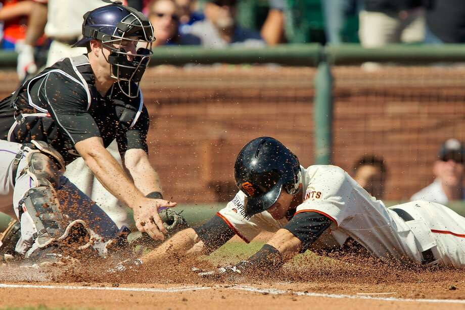SAN FRANCISCO, CA - OCTOBER 3:  Second baseman Kelby Tomlinson #37 of the San Francisco Giants dives across home plate against catcher Tom Murphy #30 of the Colorado Rockies for an in-the-park home run in the first inning at AT&T Park on October 3, 2015 in San Francisco, California.  The Giants won 3-2.  (Photo by Brian Bahr/Getty Images) Photo: Brian Bahr, Getty Images