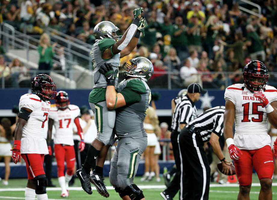 Baylor running back Johnny Jefferson, center left, and offensive tackle Spencer Drango, center right, celebrate a touchdown on a running play by Jefferson as Texas Tech defensive back Jah'Shawn Johnson (7) and defensive back Keenon Ward (15) walk back to the sideline in the second half of an NCAA college football game Saturday, Oct. 3, 2015, in Arlington, Texas. Baylor won 63-35. (AP Photo/Tony Gutierrez) Photo: Tony Gutierrez, STF / Associated Press / AP
