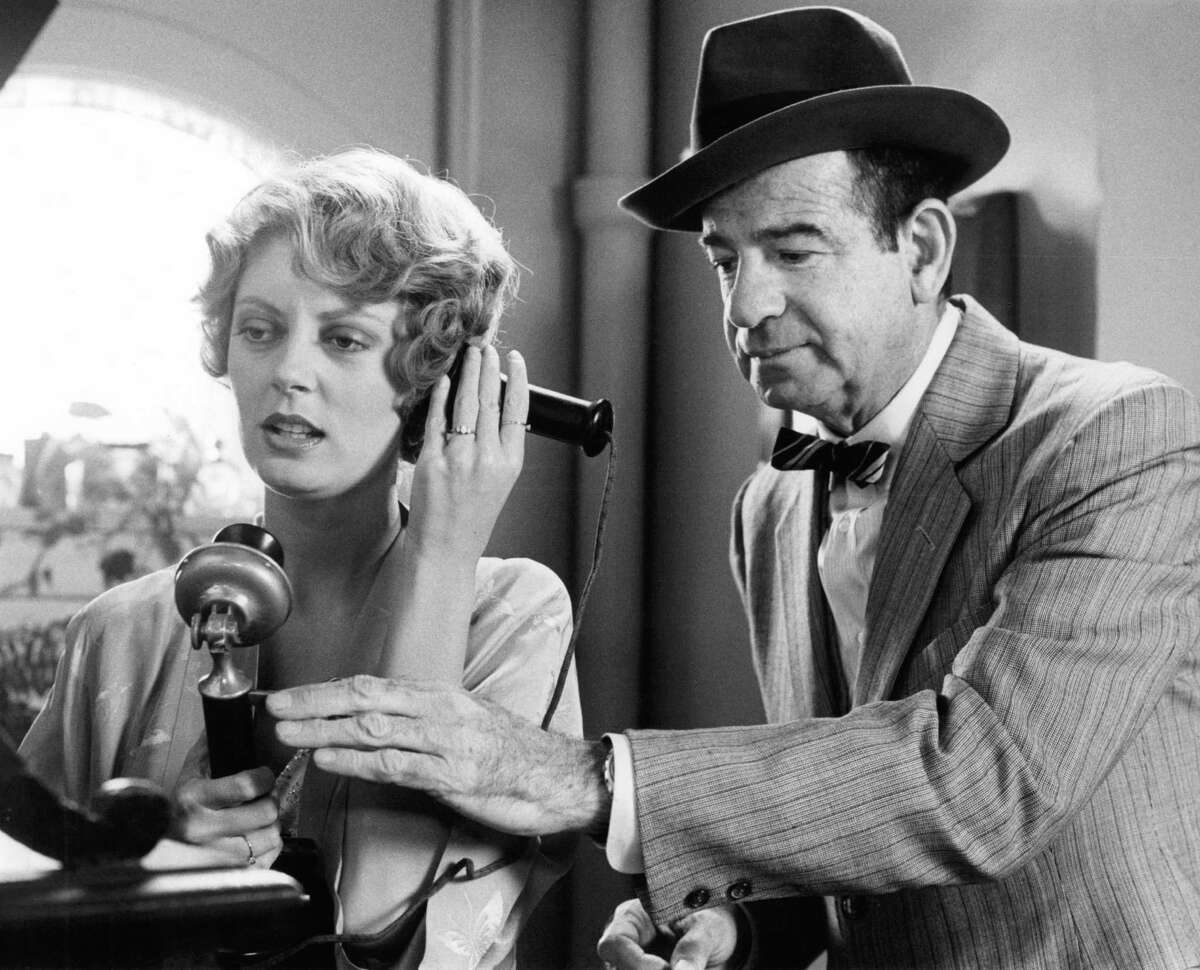 Susan Sarandon on the telephone as Walter Matthau pushes the disconnect lever in a scene from
