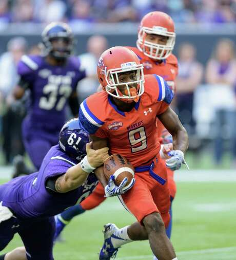 Sam Houston's Yedidiah Louis didn't let SFA's Kyle Romano prevent him from returning a punt 53 yards for a touchdown, the Bearkats' second scoring return. Photo: Wilf Thorne / © 2015 Houston Chronicle