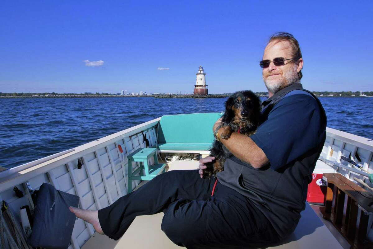 Alex Spektor is photographed with his companion Knowme on Thursday, Sept. 24, 2015 with the lighthouse his father, Eryk Spektor, purchased for $250K in 1984. The Ledge Obstruction Light was built in 1882 atop Chatham Rock, located at the entrance of Stamford Harbor on the Long Island Sound.