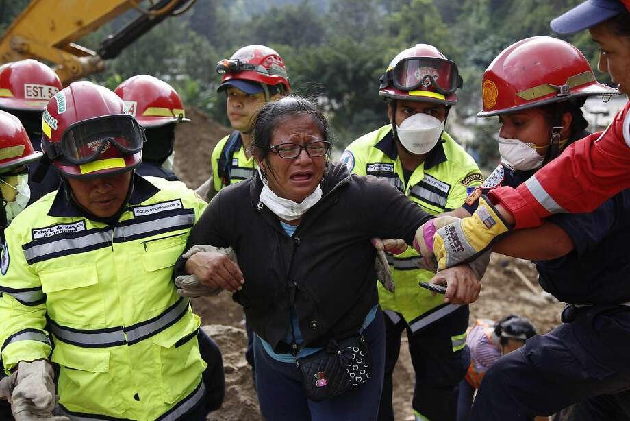 Rescuers help a woman who identified the bodies of two family members killed by a mudslide. Photo: Luis Soto, Associated Press