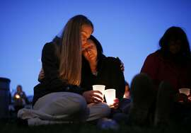 Heidi Wickersham, left, embraces her sister Gwendoline Wickersham during a prayer vigil Saturday, Oct. 3, 2015, in Winston, Ore. The vigil was held in honor of the victims of the fatal shooting at Umpqua Community College on Thursday. (AP Photo/John Locher)