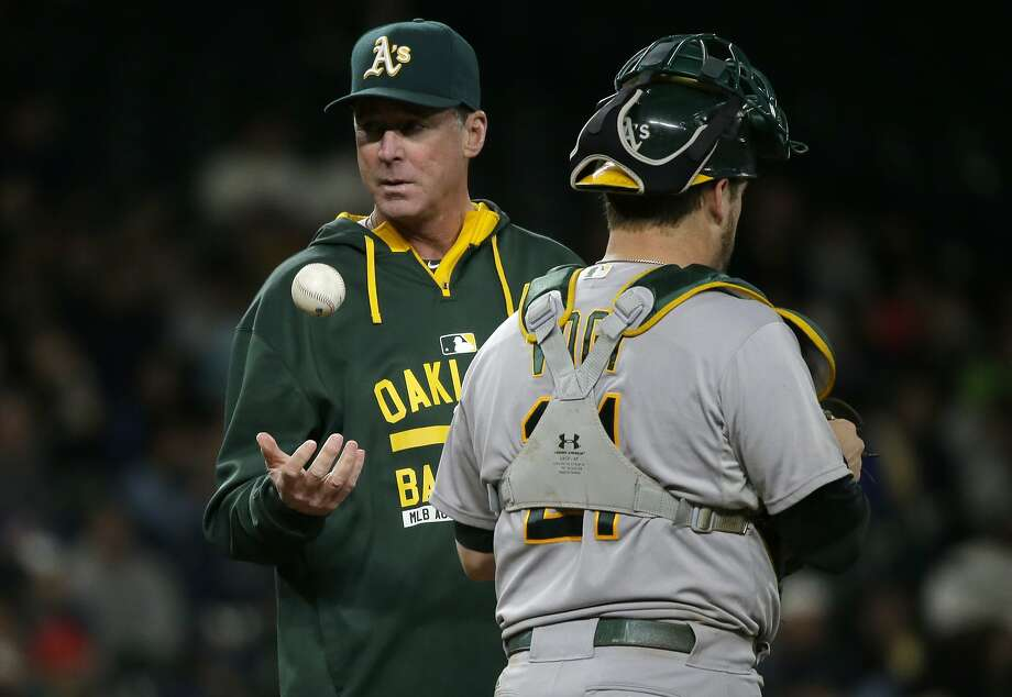 Oakland Athletics manager Bob Melvin, left, tosses the baseball as he waits with catcher Stephen Vogt for pitcher Daniel Coulombe to replace Arnold Leon on the mound in the sixth inning of a baseball game, Saturday, Oct. 3, 2015, in Seattle. (AP Photo/Ted S. Warren) Photo: Ted S. Warren, Associated Press