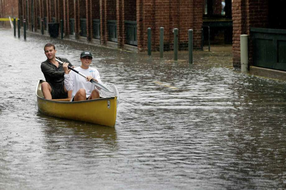 Dillon Christ, front, and Kyle Barnell paddle their canoe down a flooded street in Charleston, S.C., Saturday, Oct. 3, 2015. Rain pummeling parts of the East Coast showed little sign of slackening Saturday, with record-setting precipitation prolonging the soppy misery that has been eased only by news that powerful Hurricane Joaquin will not hit the U.S. (AP Photo/Chuck Burton) ORG XMIT: SCCB126 Photo: Chuck Burton / AP