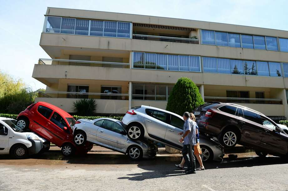 Pedestrians check out cars that were shoved into each other in Mandelieu-la-Napoule, France, after streams overflowed their banks when storms dumped more than 6.7 inches of rain. Photo: Boris Horvat, AFP / Getty Images