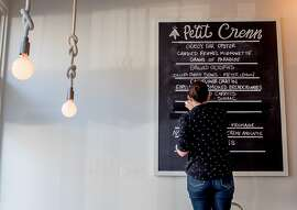 Marries Chevriere cleans the menu board at Petit Crenn in San Francisco, Calif. on Saturday, October 3rd, 2015.