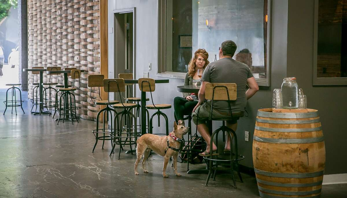 Jon Perri and Meghan Strauss have a bottle of wine with their dog Sandi at Bluxome Street Winery in San Francisco, Calif. on Saturday, October 3rd, 2015.