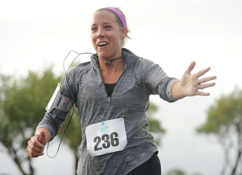 Caitlin Olson, of Fairfield, reaches out to high five her kids as she finishes the 5k 9th Annual CancerCare Fairfield Walk/Run for Hope at Jennings Beach in Fairfield, Conn. on Sunday, October 4, 2015. The event brings together family and friends in support of individuals with cancer. Photo: Brian A. Pounds, Hearst Connecticut Media / Connecticut Post