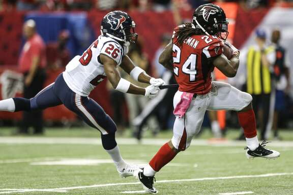 Atlanta Falcons running back Devonta Freeman (24) breaks away from Houston Texans free safety Rahim Moore (26) for a 23-yard touchdown run during the second quarter of an NFL football game at the Georgia Dome on Sunday, Oct. 4, 2015, in Atlanta. ( Brett Coomer / Houston Chronicle )
