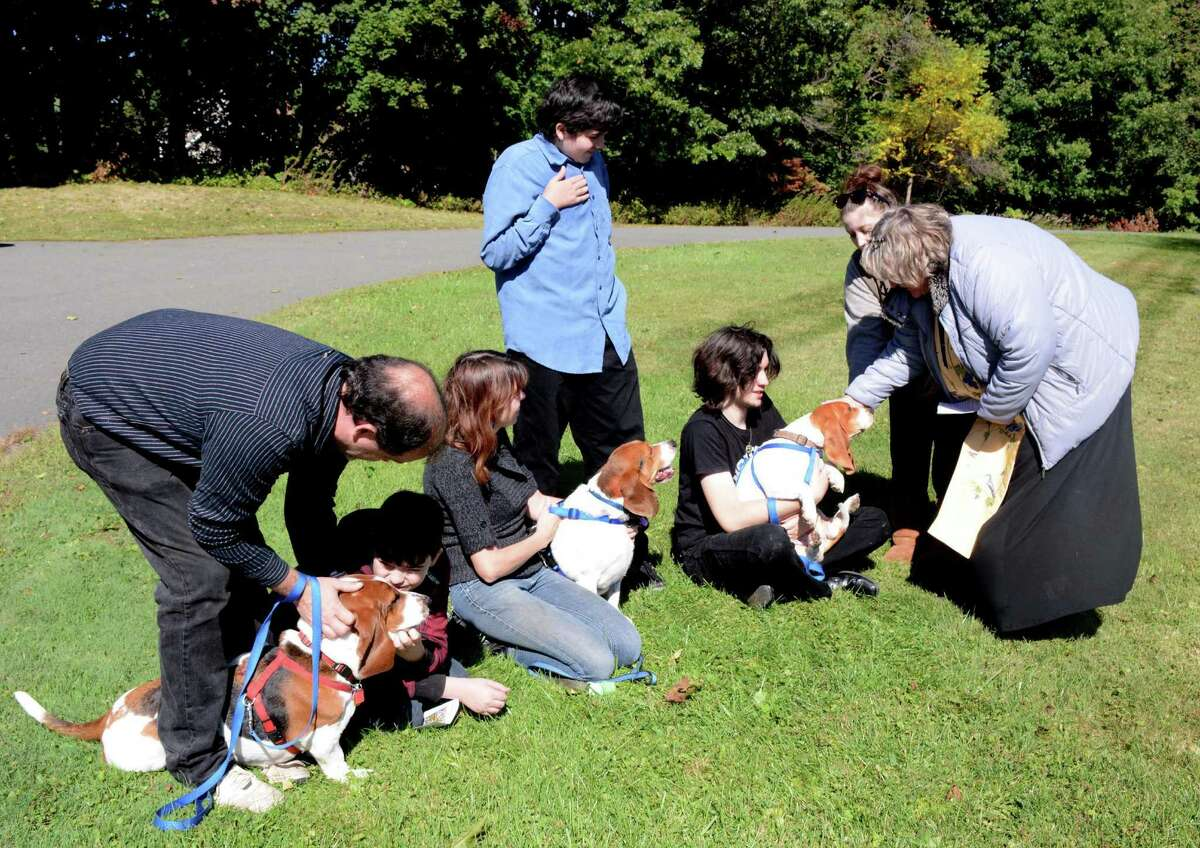 from left, Peter Hornig and his family from Danbury, Jacob, Joanne, Nathaniel, and Peter bring their bassett hounds to be blessed by Reverand Kim Bosley at the Danbury United methodist Church on Sunday, Ocotber 4, 2015.