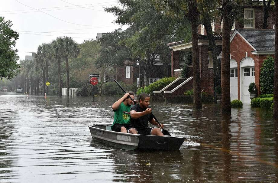 Two men row a boat on a flooded street in Charleston, S.C. More than 2 feet of rain has fallen on the region since Friday, and more is forecast. Photo: Mladen Antonov, AFP / Getty Images