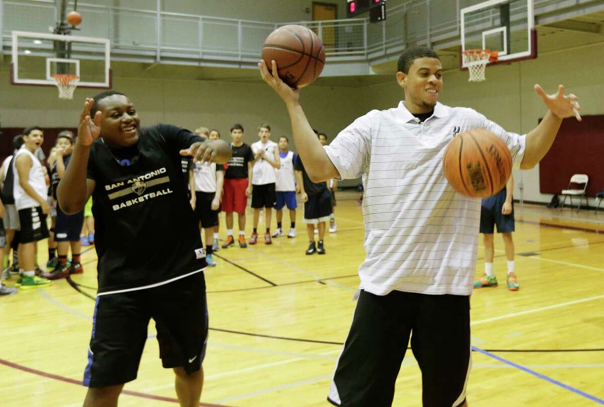 Ray McCallum (center), the Spurs' latest trade acquisition from the Sacramento Kings, plays a game with 13-year-old Caimyn Layne during a Spurs Basketball Camp at the George Gervin Youth Center on Thursday, July 23, 2015. McCallum has played two season in the NBA averaging 6.9 points, 2.7 assists and 20.7 minutes per game. The 6-foot-3 guard will likely fill the support role under Tony Parker after Cory Joseph accepted an offer with the Toronto Raptors. (Kin Man Hui/San Antonio Express-News)