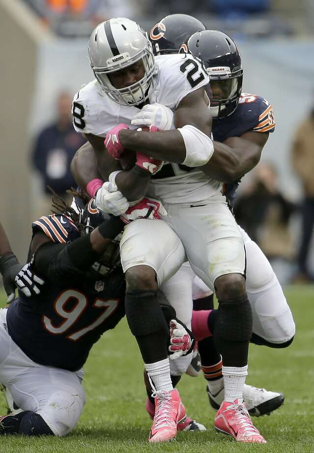 Oakland Raiders running back Latavius Murray (28) is tackled by Chicago Bears linebackers Willie Young (97), Christian Jones (59) and Shea McClellin during the second half Sunday in Chicago. Photo: Nam Y. Huh, Associated Press