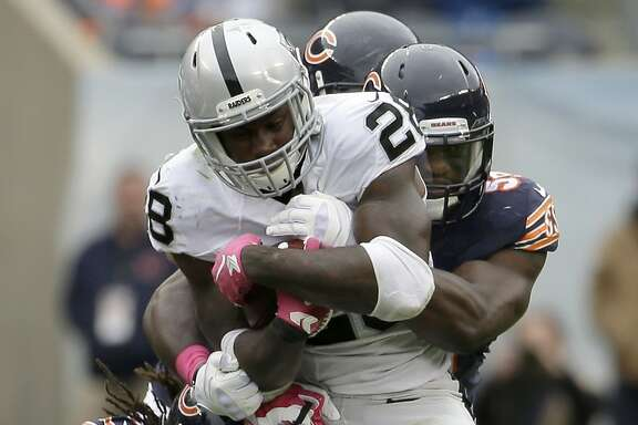Oakland Raiders running back Latavius Murray (28) is tackled by Chicago Bears linebackers Willie Young (97), Christian Jones (59) and Shea McClellin during the second half of an NFL football game, Sunday, Oct. 4, 2015, in Chicago. (AP Photo/Nam Y. Huh)