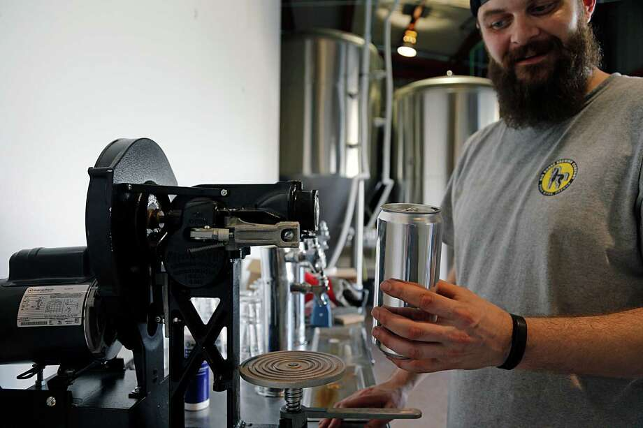 Robbie Cummings at Brash Brewing demonstrates how a crowler machine works. Photo: James Nielsen /Houston Chronicle / © 2015  Houston Chronicle