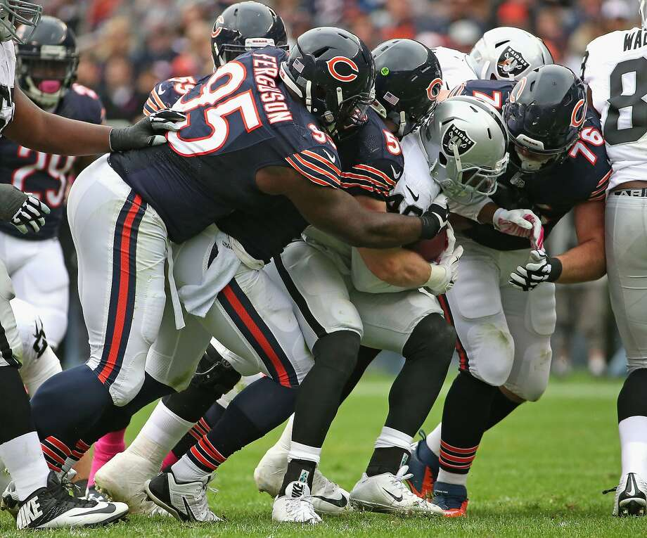 Jamize Olawale is surrounded by Bears defenders, who held Oakland to 79 yards rushing and 243 yards total offense. Photo: Jonathan Daniel, Getty Images