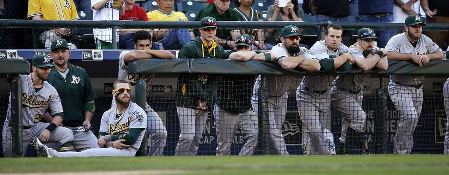 A's players watch the final out in the ninth inning of Oakland's 3-2 loss to Seattle on the final day of the regular season. Photo: Elaine Thompson, Associated Press
