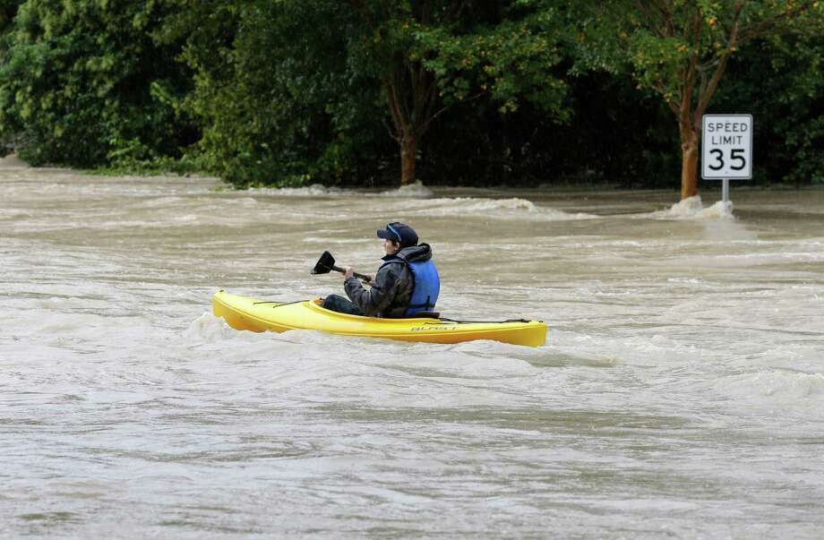 A man paddles a kayak down a flooded street in Columbia, S.C., Sunday, Oct. 4, 2015. The rainstorm drenching the U.S. East Coast brought more misery Sunday to South Carolina, cutting power to thousands, forcing hundreds of water rescues and closing many roads because of floodwaters. (AP Photo/Chuck Burton) Photo: Chuck Burton, STF / AP