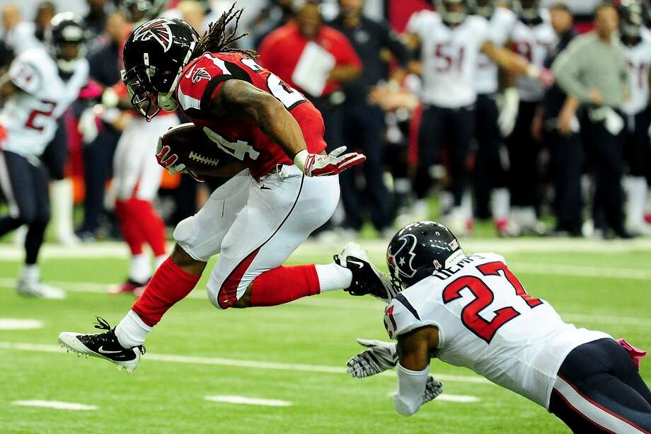 Falcons running back Devonta Freeman high steps it past Texans' Quintin Demps on his way to 149 total yards and three touchdowns. Photo: Scott Cunningham, Getty Images