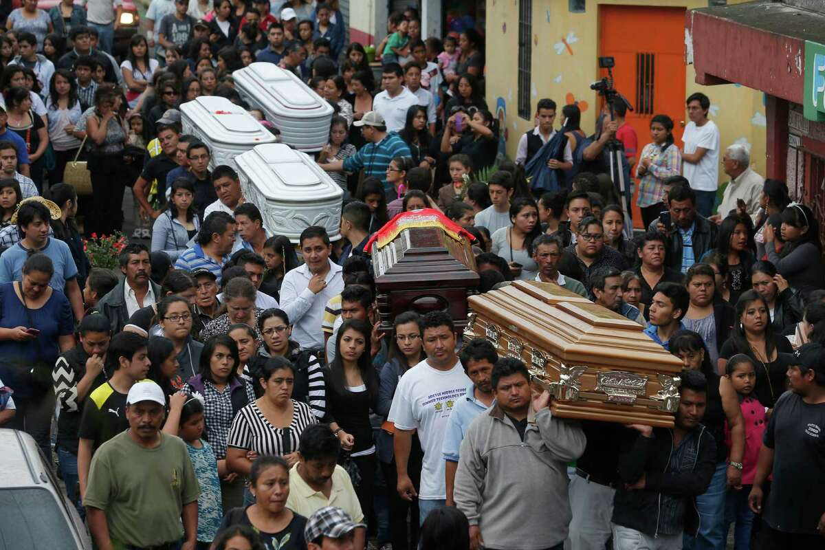 People carry the coffins of five neighbors who died in the mudslide to a cemetery on the outskirts of Guatemala City.