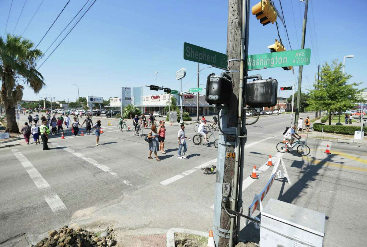 Pedestrians and bicyclists pass through the intersection of Washington and Shepherd during a May street closing as part of the Cinga Sunday Streets program organized by Houston Health Department officials.