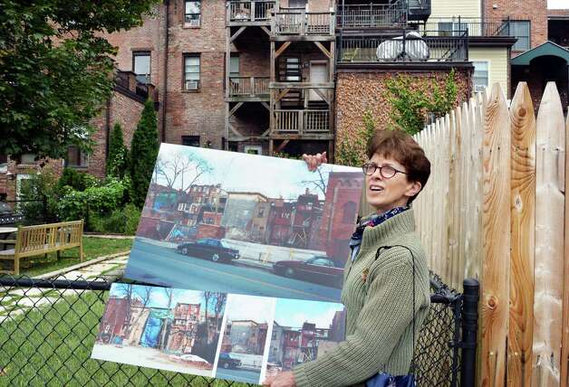 Lynn Kopka, councilwoman and president of Washington Park Neighborhood Association, holds photos from a decade ago in the rear of the renovated Washington Park block Friday, Oct. 2, 2015, in Troy, NY.  (John Carl D'Annibale / Times Union) Photo: John Carl D'Annibale / 10033551A