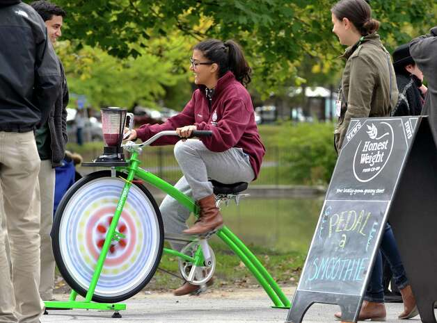 Vivek Bose, left, looks on as Rani Berry, both from Albany, pedals a Rock the Bike blender to make a fruit smoothie for the two of them  in Washington Park during the Honest Weight Food Co-op Harvest Fest on Sunday, Oct. 4, 2015, in Albany, N.Y.  The event features booths with items from the co-op along with other food and product vendors.  (Paul Buckowski / Times Union) Photo: PAUL BUCKOWSKI / 10033602A