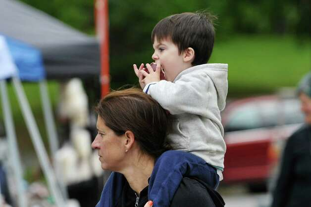 Tommy Person, 2, of Guilderland bites down on an apple as he sits on his mom's, Melinda Person, shoulders  in Washington Park during the Honest Weight Food Co-op Harvest Fest on Sunday, Oct. 4, 2015, in Albany, N.Y.  The event features booths with items from the co-op along with other food and product vendors.  (Paul Buckowski / Times Union) Photo: PAUL BUCKOWSKI / 10033602A