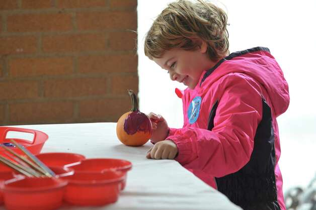 Sophia Baljin, 4, of Albany paints her pumkin  in Washington Park during the Honest Weight Food Co-op Harvest Fest on Sunday, Oct. 4, 2015, in Albany, N.Y.  The event features booths with items from the co-op along with other food and product vendors.  (Paul Buckowski / Times Union) Photo: PAUL BUCKOWSKI / 10033602A