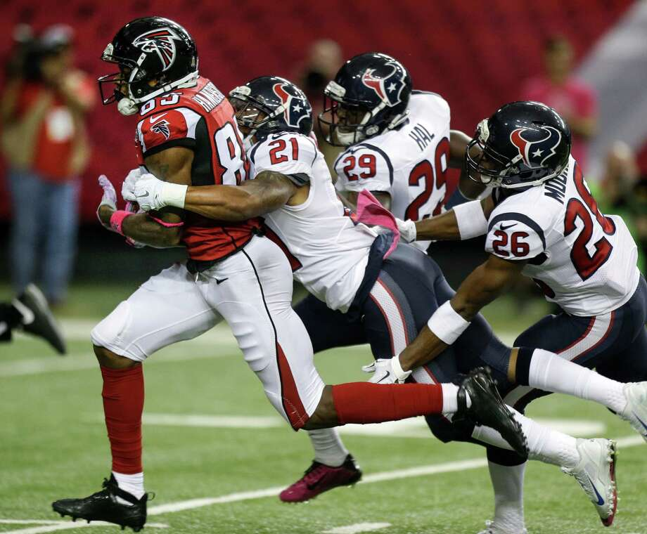 Falcons receiver Leonard Hankerson (85) is brought down by Texans defensive backs Darryl Morris (21), Andre Hal (29) and Rahim Moore (26) after a 50-yard gain in the third quarter. Photo: Brett Coomer, Staff / © 2015  Houston Chronicle