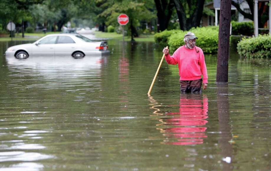 David Linnen takes a yard rake to clear drains in front of the evacuated Winyah Apartments in Georgetown, S.C. President Barack Obama has signed an emergency declaration for South Carolina. Photo: Mic Smith /Associated Press / FR2 AP