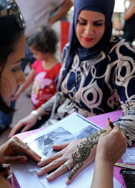 Henna artist Swati Jain (left) gives Meriem Douma a henna tattoo Sunday Oct. 4, 2015 during the Muslim Cultural Heritage Society's 6th annual Eid Festival 2015 held at Mayor Maury Maverick Plaza in La Villita. Photo: Edward A. Ornelas, Staff / San Antonio Express-News / © 2015 San Antonio Express-News