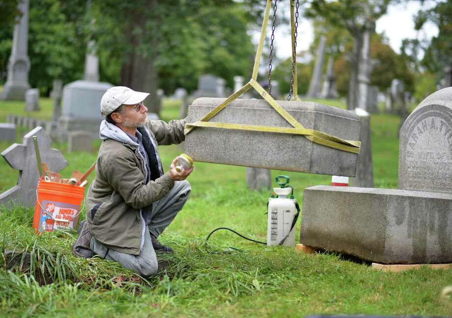 Joe Ferranninie, owner of Grave Stone Matters of Hoosick Falls, works to reset an unsafe grave stone from 1875 in Albany Rural Cemetery Thursday Oct. 1, 2015 in Menands, NY.  (John Carl D'Annibale / Times Union) Photo: John Carl D'Annibale / 10033566A