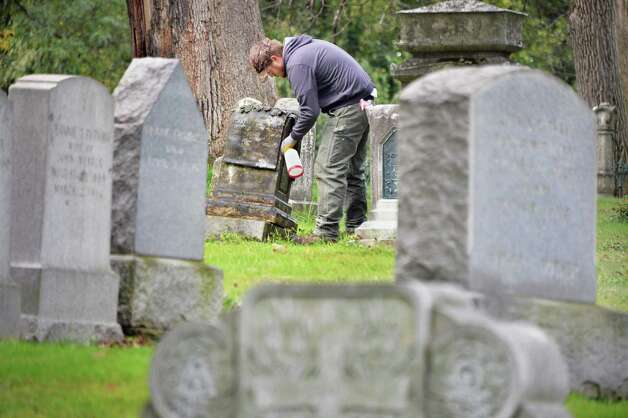 Pat Taber of Grave Stone Matters of Hoosick Falls, cleans an old grave stone before resetting it in Albany Rural Cemetery Thursday Oct. 1, 2015 in Menands, NY.  (John Carl D'Annibale / Times Union) Photo: John Carl D'Annibale / 10033566A