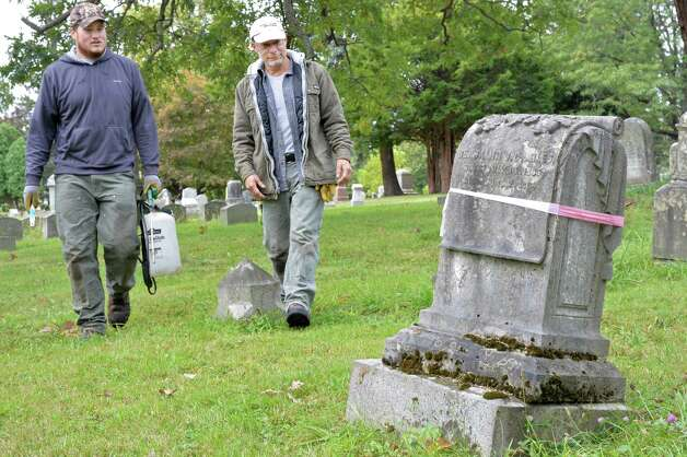 Intern Pat Taber, left, and Joe Ferranninie, owner of Grave Stone Matters of Hoosick Falls, approach the unsafe grave stone of Benjamin Miles from 1864 in Albany Rural Cemetery Thursday Oct. 1, 2015 in Menands, NY.  (John Carl D'Annibale / Times Union) Photo: John Carl D'Annibale / 10033566A