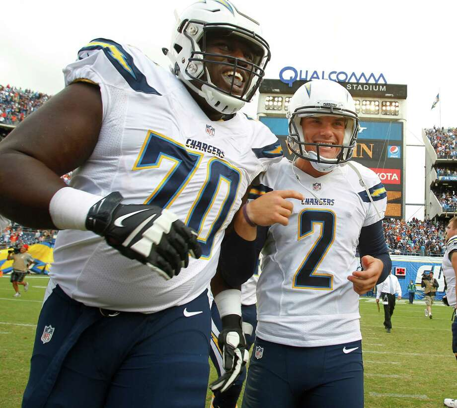 Chargers kicker Josh Lambo (2) is all smiles as he is escorted off the field by equally happy tackle King Dunlap after Lambo booted the game-winning field goal to beat Cleveland 30-27 at San Diego. Photo: K.C. Alfred, MBR / San Diego Union-Tribune