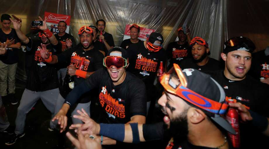 Astros shortstop Carlos Correa, center, and teammates dance in celebration in the locker room after securing an American League wild-card berth despite a 5-3 loss to the Diamondbacks on Sunday at Chase Field in Phoenix. Photo: Karen Warren, Staff / © 2015 Houston Chronicle