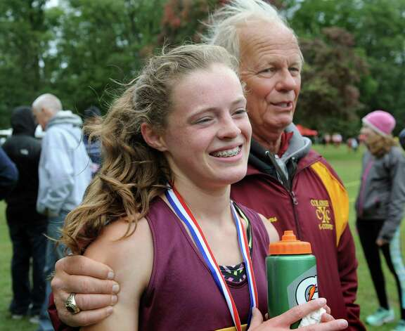 Colonie's Kathryn Tenney, center, gets a hug from her coach Frank Myers, right, after she wins the girls' division II race during the Grout Invitational Cross Country Race on Saturday, Oct. 3, 2015, in Schenectady, N.Y. (Cindy Schultz / Times Union) Photo: Cindy Schultz / 10033573A