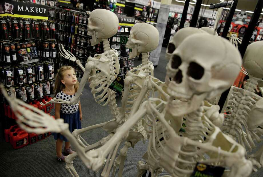 Olivia Vlaicu, 6-year-old of Maywood, N.J., takes an interest in real-looking Halloween skeletons at the Spirit Halloween store in Paramus, N.J. Spirit Halloween, a chain of more than 1,150 pop-up shops across the country, has reincarnated a former Staples store and filled it with 4,000 costumes and accessories with themes ranging from zombies to superheroes and princesses to prison inmates. Photo: Mel Evans /Associated Press / AP