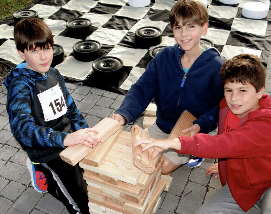 Fairfielders John Kuhl, Rory Tamulis and Ewan Dignon, all 10, play a game of Jenga at CancerCare's Walk/Run for Hope on Sunday at Jennings Beach. Photo: Mike Lauterborn / For Hearst Connecticut Media / Fairfield Citizen
