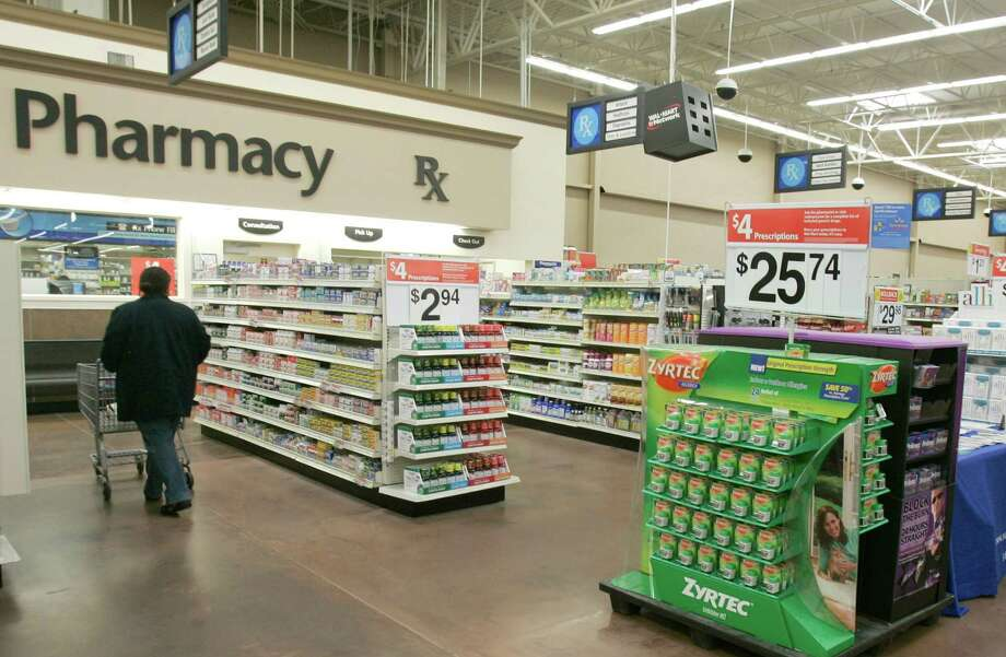 A shopper walks toward the pharmacy at a Walmart store in Little Rock, Arkansas. A recent Avalere Health report found the average monthly premiums for the 10 most popular Medicare prescription drug plans will exceed $40 for the first time in 2016. Photo: Associated Press File Photo / AP