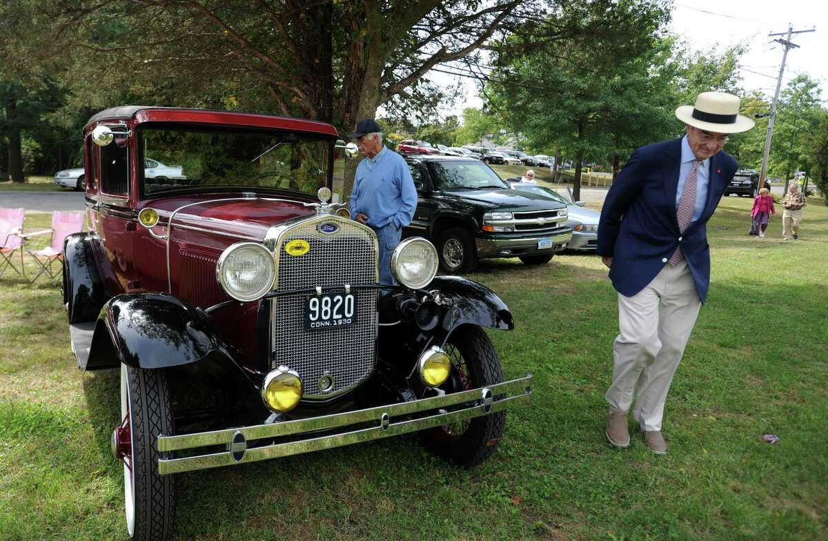 Peter L. Malkin, of Greenwich, chairman of the Merritt Parkway Conservancy, walks past a display of antique cars whose drivers joined in the recent 75th anniversary celebration of the highway in Stratford.