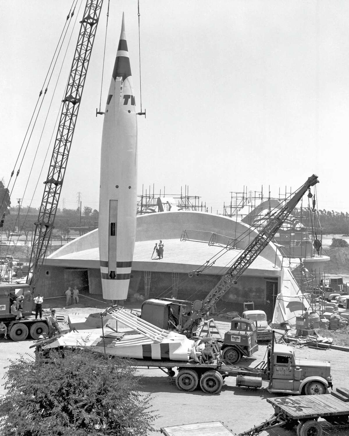 """1955: Only days before opening July 17, a crane lifts the """"Rocket to the Moon"""" during construction of Tomorrowland in Disneyland."""