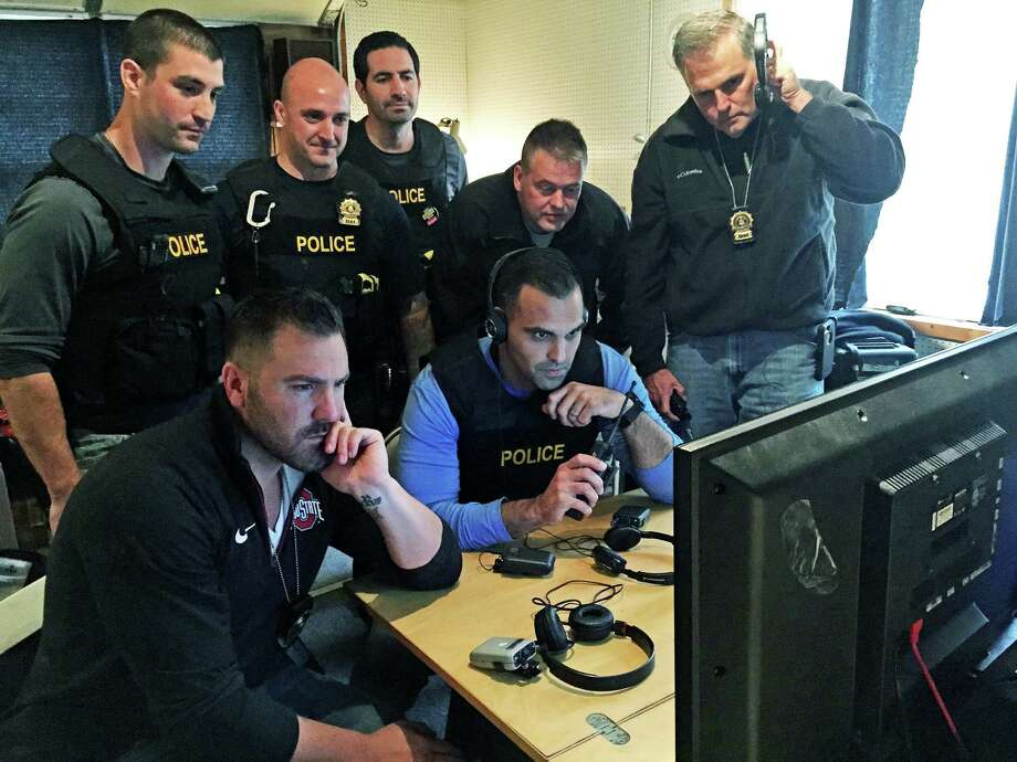 Detectives from the Fairfield Police Department keep an eye on activity during an undercover sting operation that snagged 10 men who came to a house in town, expecting to have sex with a minor. Photo: Contributed Photo / Fairfield Citizen /  Fairfield Citizen contributed